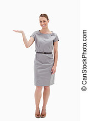 Smiling woman in a dress presenting something with her hand...