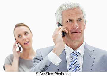 Close-up of a white hair businessman talking on the phone with a woman in background