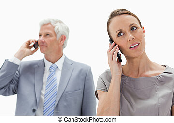 Close-up of a woman on the phone with a white hair businessman