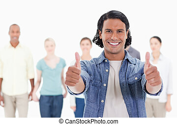 Close-up of a man with his thumbs-up with people behind...