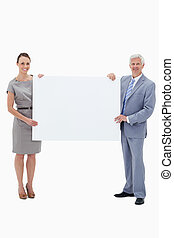 White hair businessman smiling and holding a big white sign...