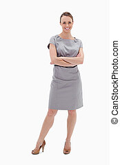 Smiling woman in dress with her arms folded against white...
