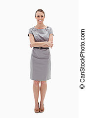 Woman in dress smiling with her arms folded