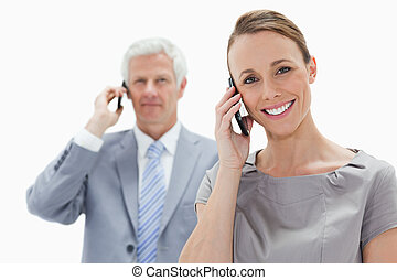 Close-up of a smiling woman making a call with a white hair man in background