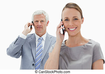 Close-up of a white hair businessman making a call with a smiling woman in foreground against white background