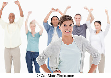 Woman with her hands on hips with people behind raising their arms against white background