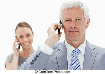 Close-up of a white hair businessman on the phone with a smiling woman in background