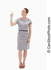 Smiling woman in dress showing something above with her hand...
