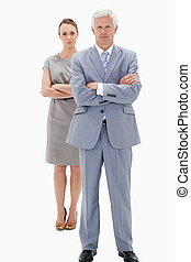 White hair businessman with a woman in background crossing...