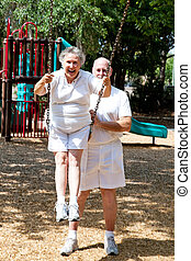 Senior Couple - Playground Fun - Senior woman gets a push on...