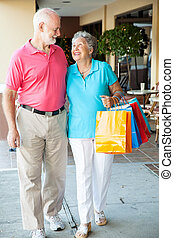 Happy Senior Shoppers - Senior couple strolling along with...