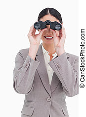 Businesswoman looking through binoculars
