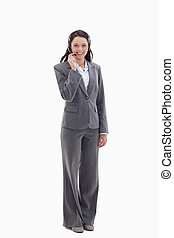 Businesswoman smiling and speaking with a headset against...