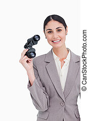 Smiling businesswoman with spy glasses against a white...