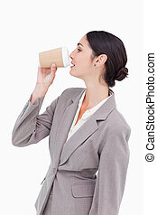 Side view of businesswoman taking a sip out of a paper cup...