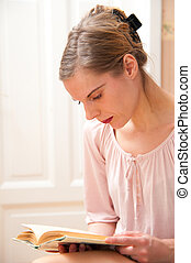 Attractive young woman reading a book, portrait