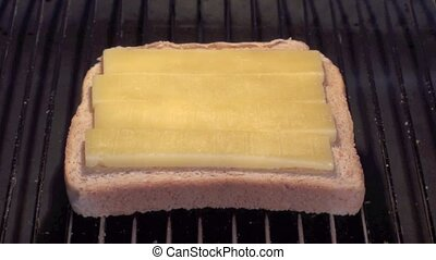 Cheese on toast - Slice of toast with cheese melting under a...