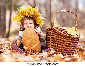 baby with a loaf - cute baby girl having a picnic, sitting...