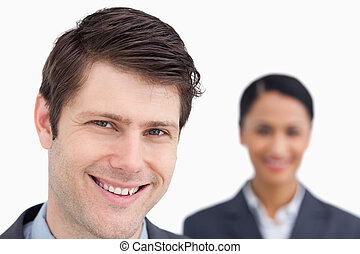 Close up of smiling salesman with colleague behind him