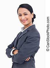 Close up of smiling saleswoman with arms crossed against a...