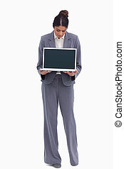 Female entrepreneur looking at her laptop in her hands