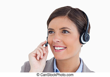 Close up of smiling female call center agent with headset...