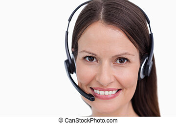 Close up of smiling female call center employee against a...