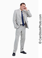 Smiling businessman on his cellphone against a white...