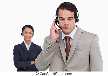 Hotline employee with colleague behind him against a white...