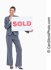 Happy real estate agent with sold sign against a white...