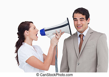 Saleswoman with megaphone yelling at colleague against a...