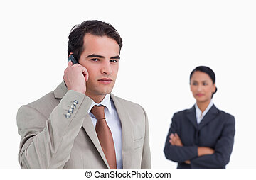Serious salesman on his cellphone with colleague behind him