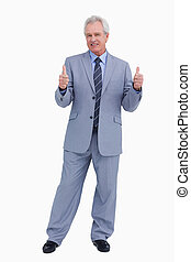 Smiling mature tradesman giving thumbs up against a white...