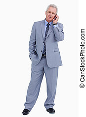Mature tradesman on his cellphone against a white background
