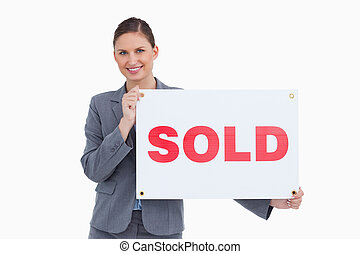 Smiling real estate agent holding sold sign against a white...