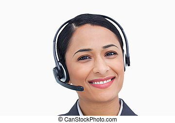 Close up of smiling call center agent against a white...