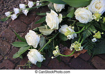 White roses and lilies in sympathy flower arrangement -...