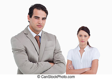 Salesman with arms crossed and colleague behind him