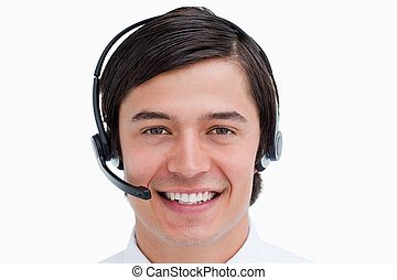 Close up of smiling male call center agent with headset on...