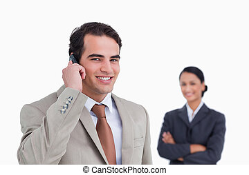 Smiling salesman on his cellphone with colleague behind him