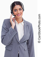 Smiling female call center employee against a white...