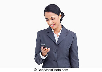 Close up of smiling saleswoman reading text message against...