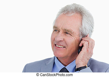 Close up of mature tradesman talking on his mobile phone...