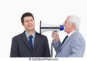 Close up of mature businessman with megaphone yelling at...
