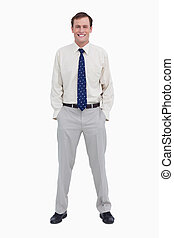 Smiling young businessman with his hands in his pockets