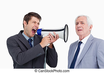 Close up of businessman with megaphone yelling at his boss...