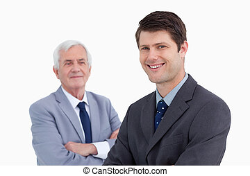 Close up of smiling businessman with his mentor behind him...