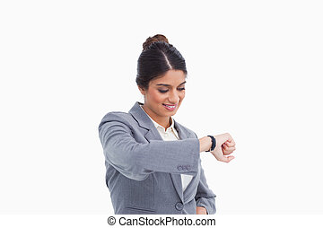 Smiling female entrepreneur looking at her watch against a...