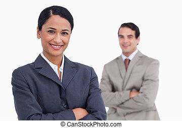 Smiling saleswoman with arms folded and colleague behind her...