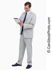 Smiling businessman using tablet computer against a white...
